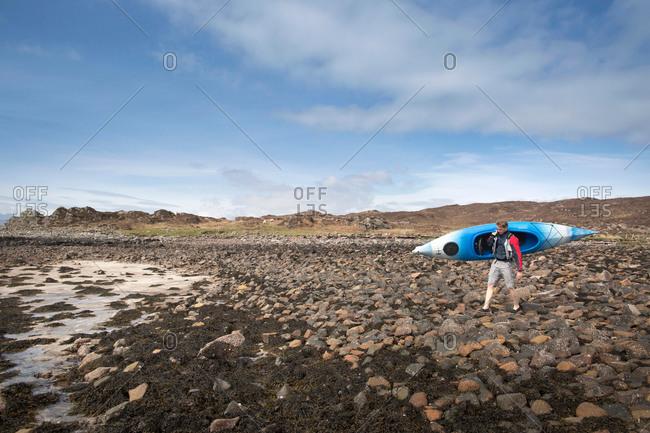 Mid adult man carrying canoe, Loch Eishort, Isle of Skye, Hebrides, Scotland