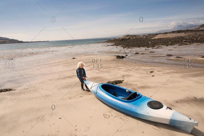 Boy with canoe on beach, Loch Eishort, Isle of Skye, Hebrides, Scotland