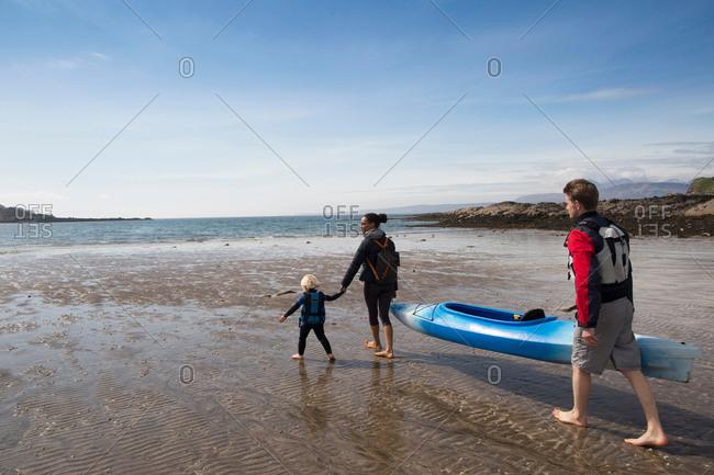 Family with canoe on beach, Loch Eishort, Isle of Skye, Hebrides, Scotland
