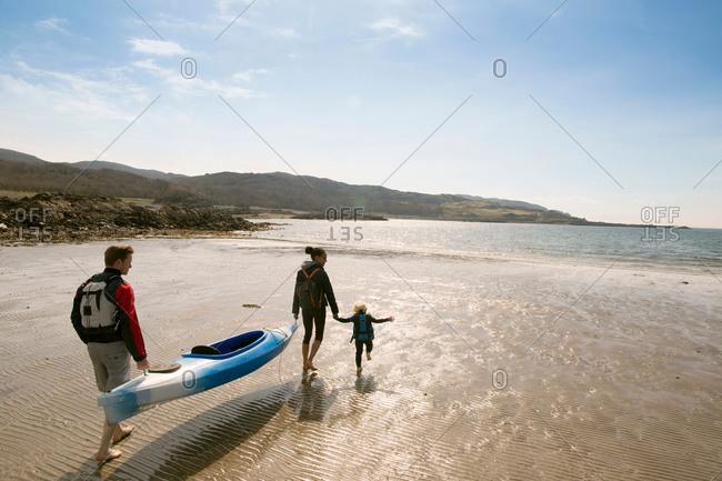 Family on beach with canoe, Loch Eishort, Isle of Skye, Hebrides, Scotland