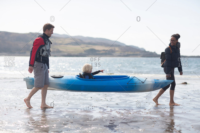 Parents carrying son in canoe on beach, Loch Eishort, Isle of Skye, Hebrides, Scotland