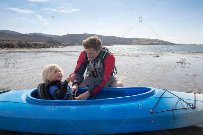 Father helping son in canoe, Loch Eishort, Isle of Skye, Hebrides, Scotland