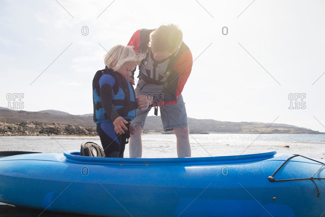 Father helping son adjust lifejacket in canoe, Loch Eishort, Isle of Skye, Hebrides, Scotland