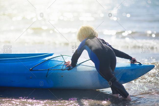 Boy in water pushing canoe