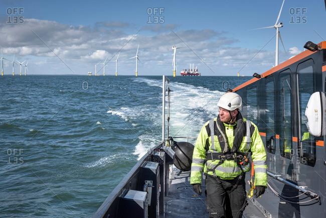 Crew member walking on deck of boat on offshore wind farm