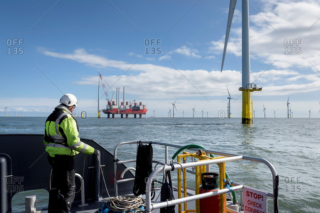 Worker looking out from ship to offshore wind farm and construction ship