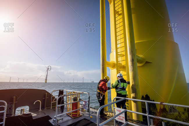 Engineers preparing to climb wind turbine at offshore wind farm
