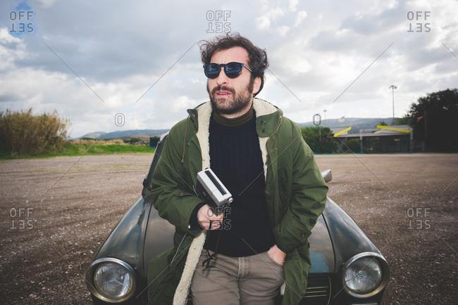 Mid adult man leaning against vintage car with vintage movie camera