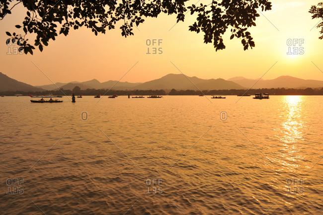Boats on lake at sunset, Hangzhou, China