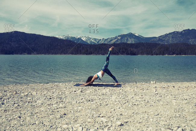 Mid adult woman, beside lake, in yoga position