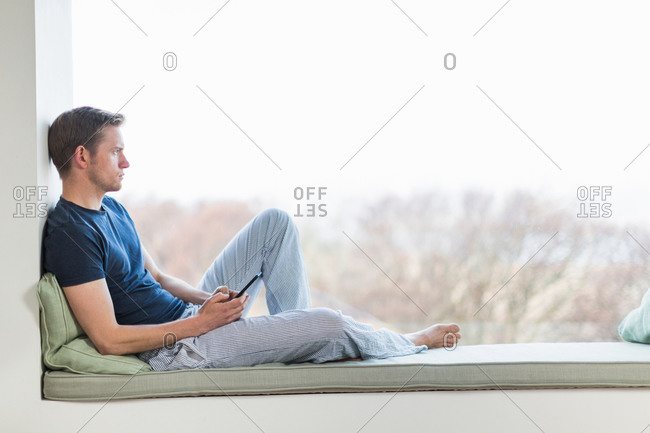 Mid adult man sitting on window seat, looking out of window