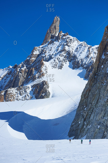 Distant view of three skiers on Mont Blanc massif, Graian Alps, France