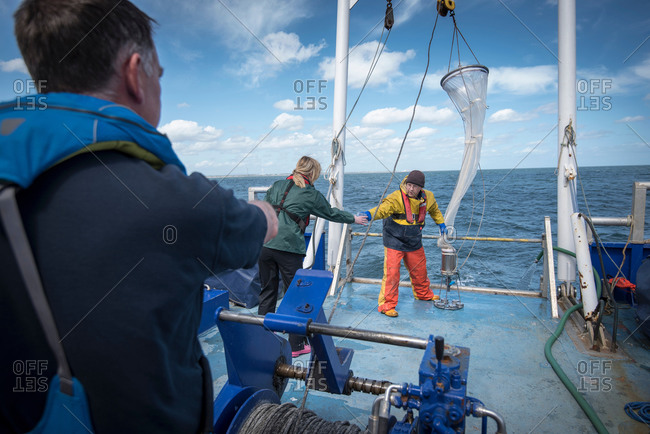 Research marine biologists taking samples from plankton net on research ship