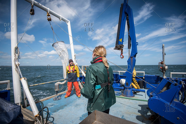 Marine biologists taking samples from plankton net on a ship