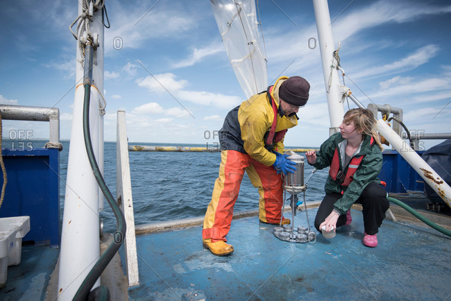 Marine biologists sampling plankton from net on research ship