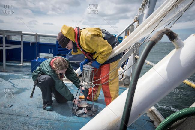 Marine biologist sampling plankton from net on research ship