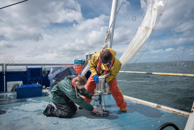 Marine biologist taking plankton samples from net on research ship