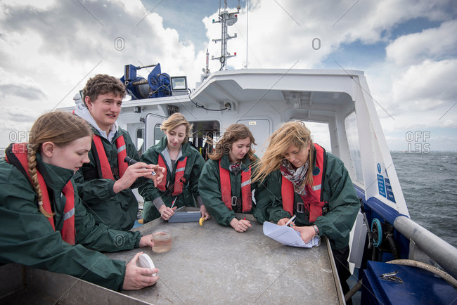Marine biologists students inspecting plankton samples on research ship