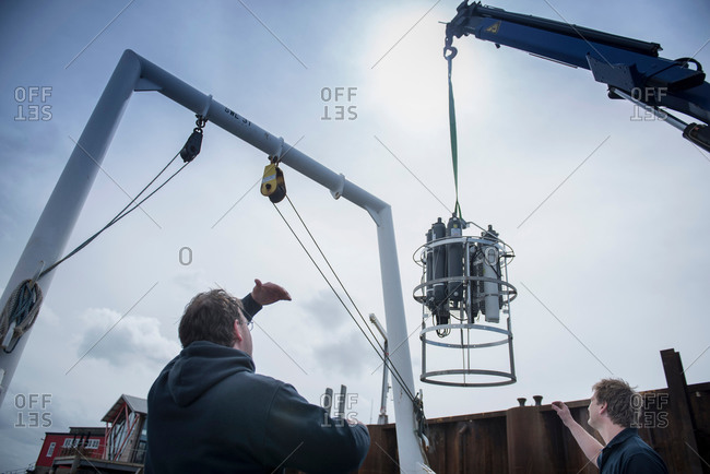 Workers loading research equipment aboard research ship, low angle view