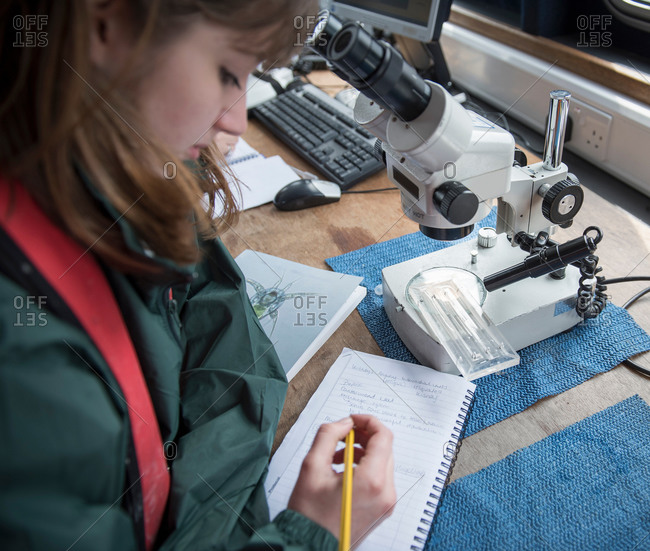 Female scientist inspecting sample of plankton with microscope on research ship