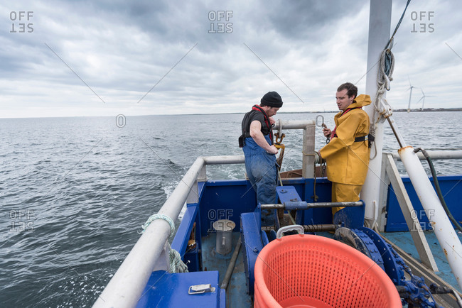 Research scientist and fisherman pay out trawl net on research ship