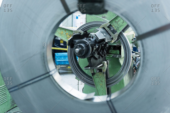 Rolls of steel in stamping machine in engineering factory, close up