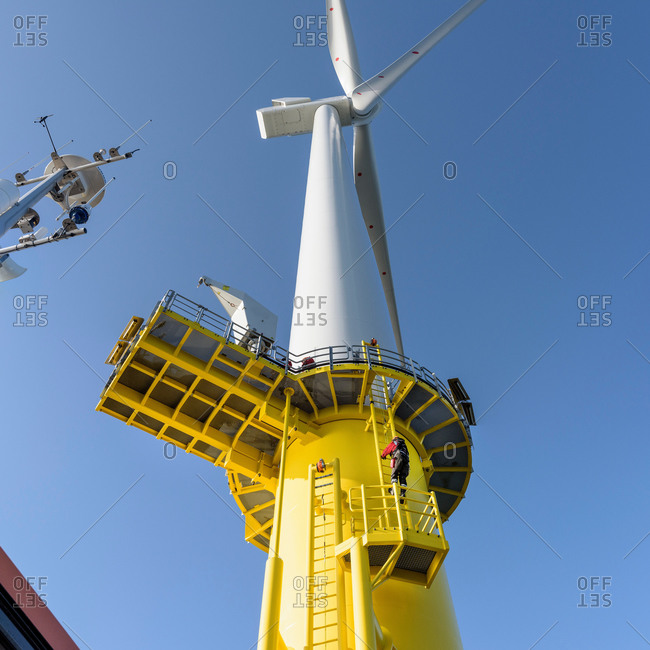 Engineer climbing wind turbine from boat at offshore windfarm, low angle view
