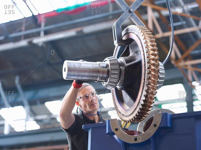 Worker assembling industrial gearbox in engineering factory