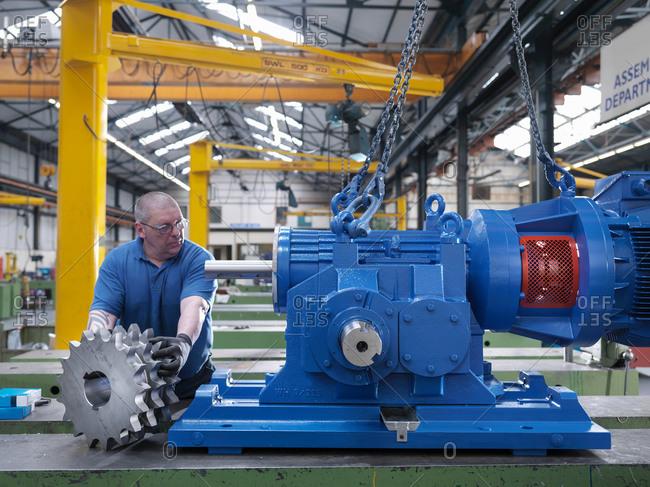 Engineer assembling industrial gearbox in engineering factory