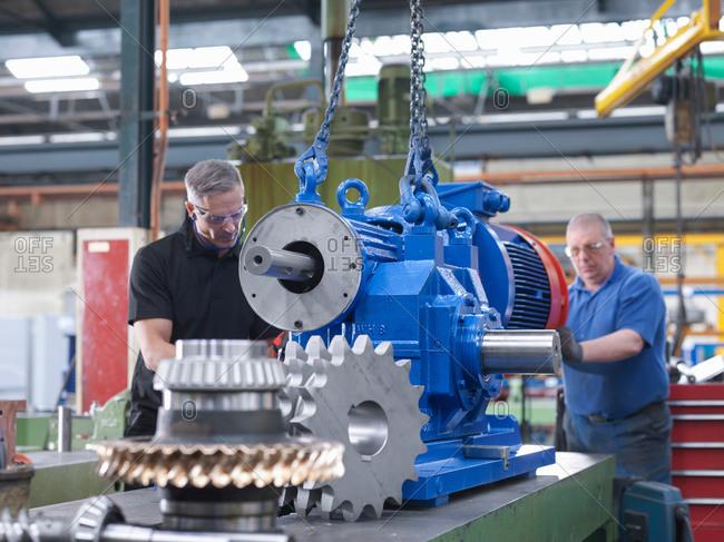 Two engineers assembling industrial gearbox in engineering factory
