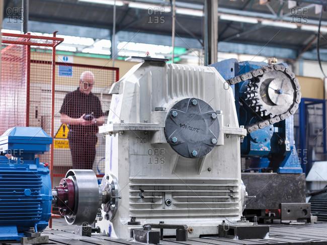 Engineer testing industrial gearbox in engineering factory