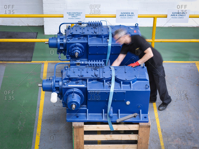 Engineer preparing gearboxes for shipping in engineering factory