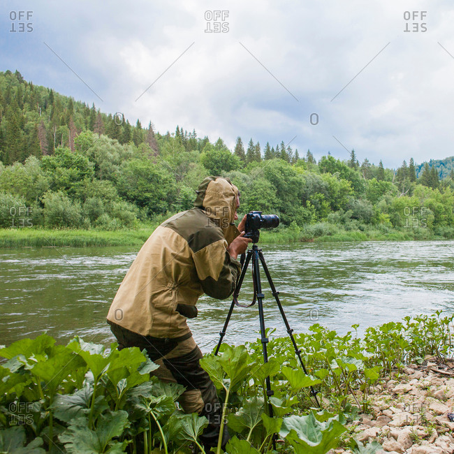 Male photographer photographing rural river