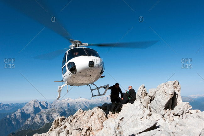 Helicopter dropping BASE jumpers on mountain, Dolomites, Italy