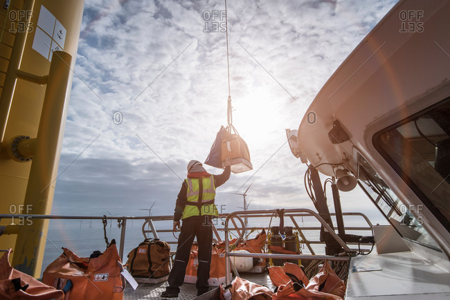 Deck worker winching parts up to wind turbine on offshore windfarm