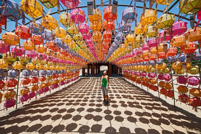 Female tourist looking at rows of lanterns honoring buddha birthday in Naksansa Temple, Naksansa, Yangyang, Gangwon province, South Korea