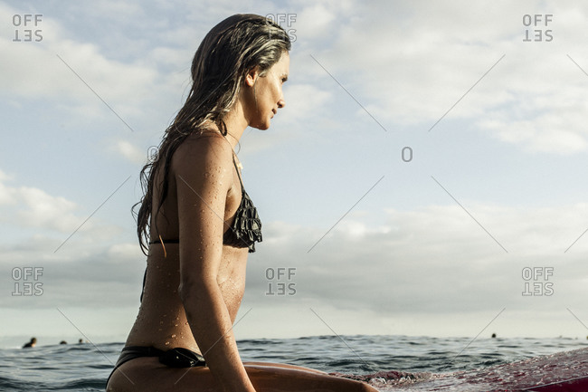 Latin American girl waits for a wave on her surf board while surfing at sunset