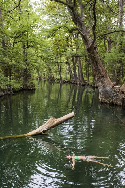 A young woman enjoys a calm swimming hole, the Blue Hole, near Wimberley, Texas.