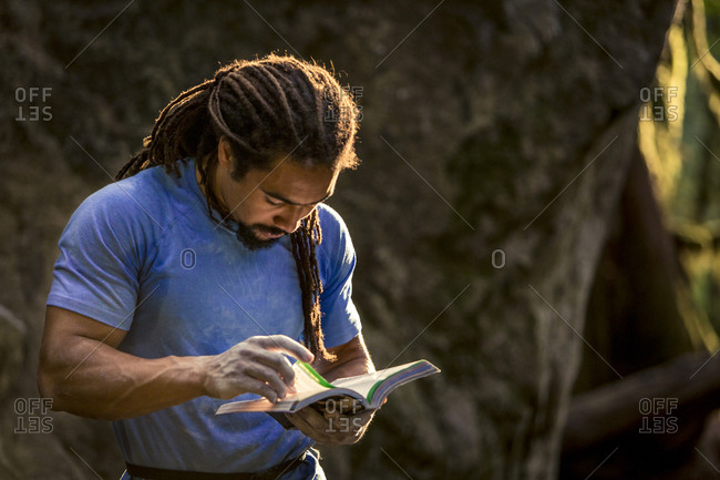African American rock climber looks thought the guide book in search of the next climbing problem.