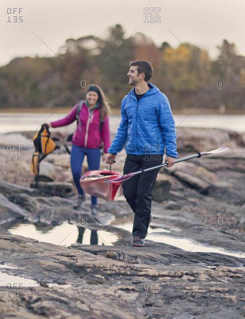 A young couple hauls their boat along the shore after a paddle along the Maine coast.