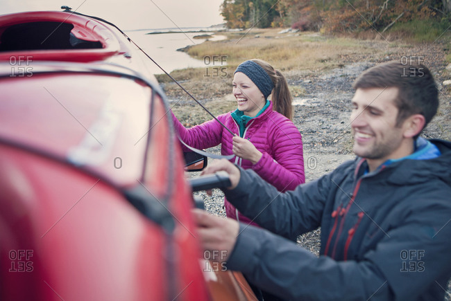 A young couple loads their boat on the car after a paddle along the Maine coast.