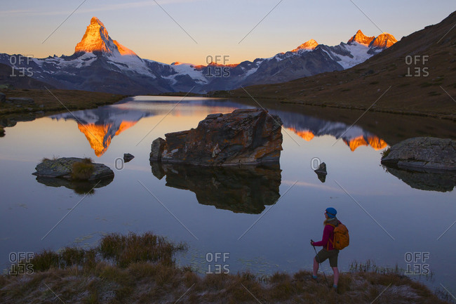 A female hiker is enjoying the gorgeous view of the sunrise on the Matterhorn mountain, while standing at the Stellisee lake above Zermatt in the Swiss Alps.