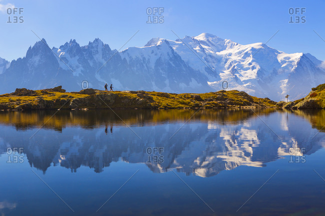 Two hikers in front of Mont Blanc which is reflected in a scenic mountain lake near Chamonix, France.