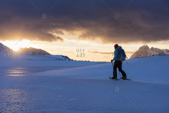 Female hiker with snowshoes at winter dawn on way to Ryten, Moskenesay, Lofoten Islands, Norway