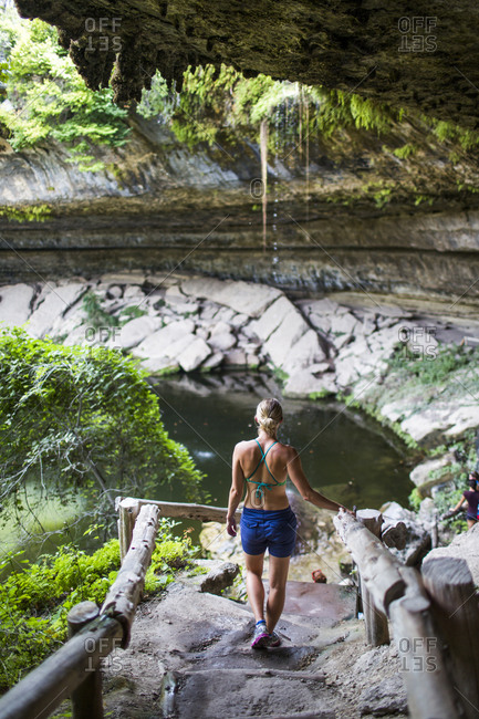 A young woman enjoys the Hamilton Pool near Wimberley, Texas on a hot day.