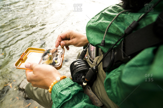 A fly fisherman looks through his fly box.
