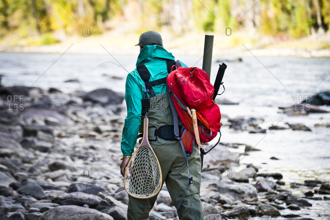 A fisherman walks upstream with his gear.