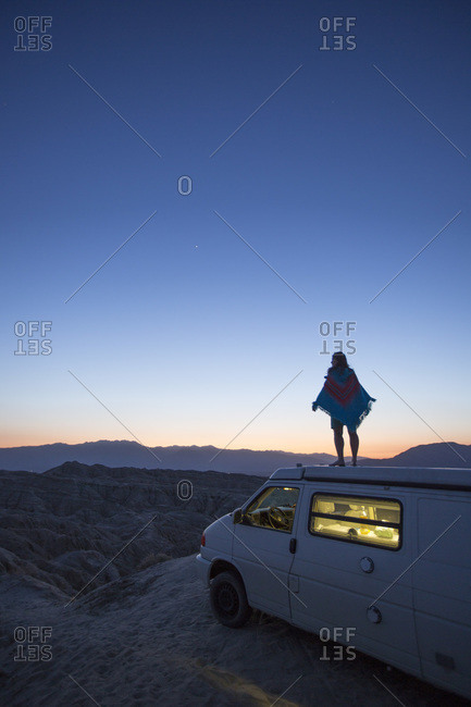 A woman taking in the night from atop a camper van.