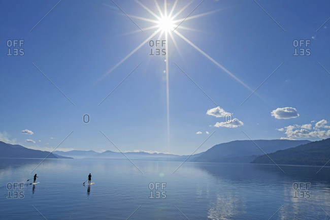 Two people paddle boarding on a calm lake.