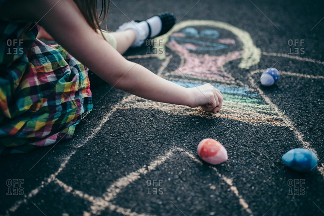 Close-up of a girl drawing on the ground with sidewalk chalk